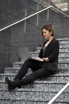 Woman with laptop on stairs full shot