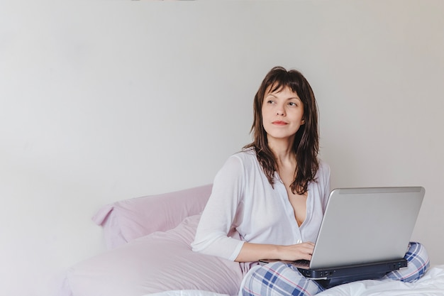 Woman with laptop thinking