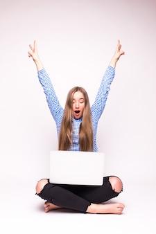 Женщина с ноутбуком, выигравшим с успехом. празднование, сидя со скрещенными ногами на полу - изолированные на белой стене.