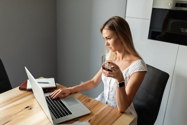 Женщина с ноутбуком работает и учится в домашнем офисе