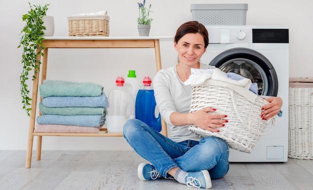 Женщина с корзиной для белья, сидя на полу перед стиральной машиной в помещении