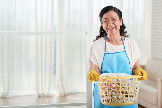 Woman with laundry basket smiling at camera