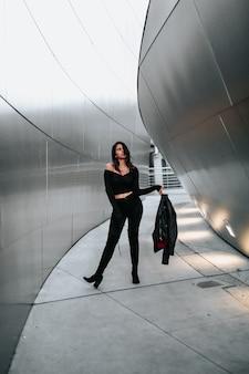 鋼の建物に革のジャッカーを持つ女性