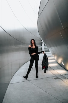 Woman with leather jacker on steel building