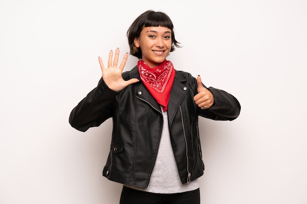 Woman with leather jacket and handkerchief counting six with fingers