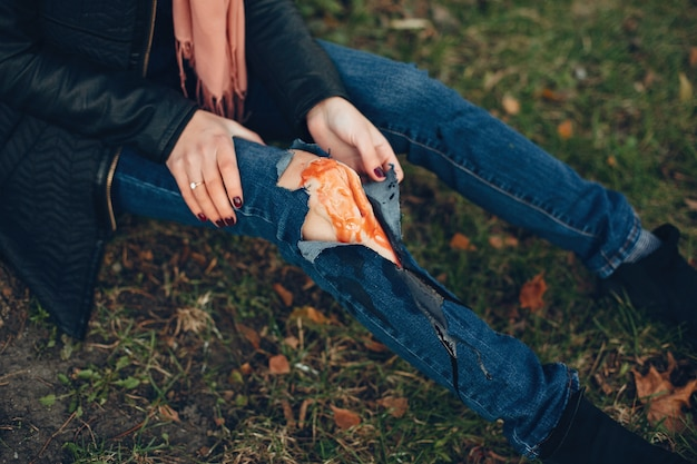 Woman with a leg injury. the wounded girl sitting by the tree. the wound is bleeding.