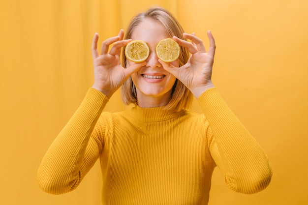 Woman with lemon slices in front of eyes in a yellow scene
