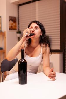 台所のテーブルでたくさんのアルコールを飲む人生の問題を抱えた女性。アルコール依存症の問題で疲れ果てた不幸な人の病気と不安感。