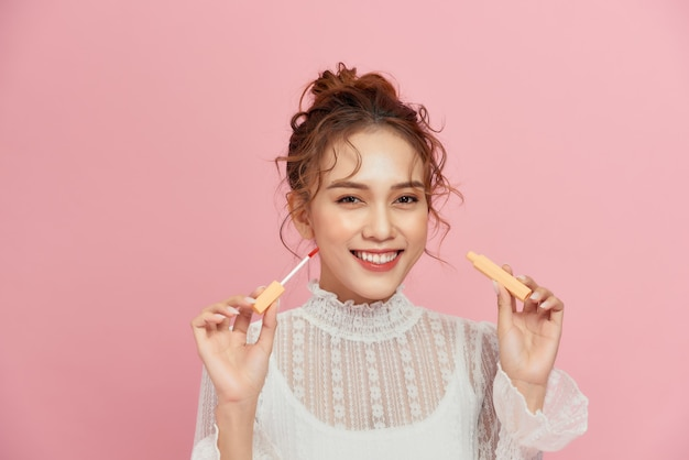 Woman with lip gloss. photo of woman with perfect makeup on pink