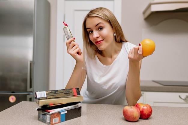 キッチンで口紅とリンゴを持つ女性