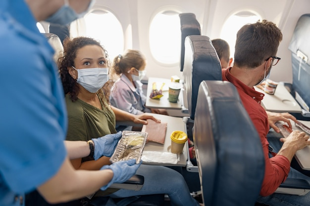 乗客に昼食を提供している女性の客室乗務員を見ている保護フェイスマスクを身に着けている小さな娘を持つ女性。 covid19パンデミック時の飛行機での旅行