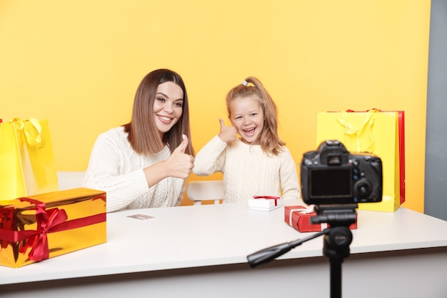 Woman with little girl blogger sitting together in the studio and showing thumb up sign