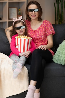 Woman with a little girl wearing 3d glasses watching tv and eating popcorn. family time relax with young girl kid on sofa in living room concept.