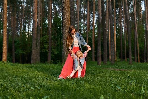 어린 딸을 둔 여자가 공원의 잔디밭에서 걷고 춤을 춥니다.
