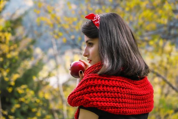 빨간 익은 사과를 손에 들고 긴 검은 머리를 가진 여자 현대 빨간 망토 또는 백설 공주