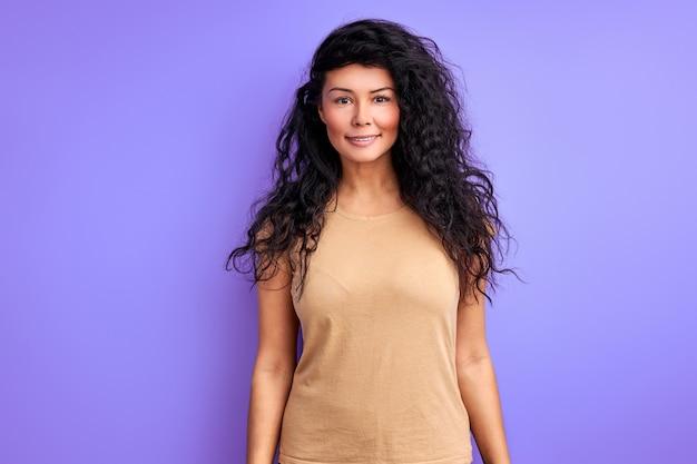 スタジオで孤立した笑顔、カジュアルな服装の女性の肖像画のポーズの長い黒髪の女性