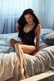 Woman with long black hair sits on a bed in black underwear