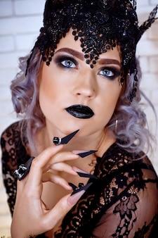 長い黒い爪と青い目を持つ女性