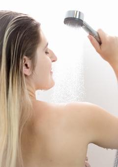 Женщина с длинными светлыми волосами принимает душ
