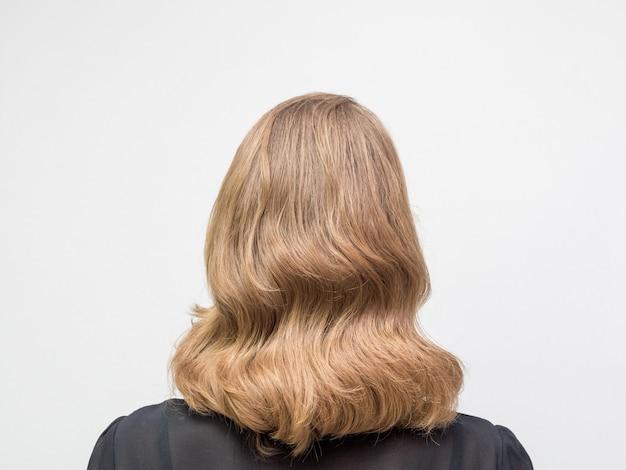 長いブロンドの髪と美容院でウェーブのかかった髪のレトロなスタイルのエレガントな髪型を持つ女性。背面図。