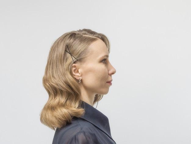 長いブロンドの髪と美容院でウェーブのかかった髪のレトロなスタイルのエレガントな髪型を持つ女性。側面図。