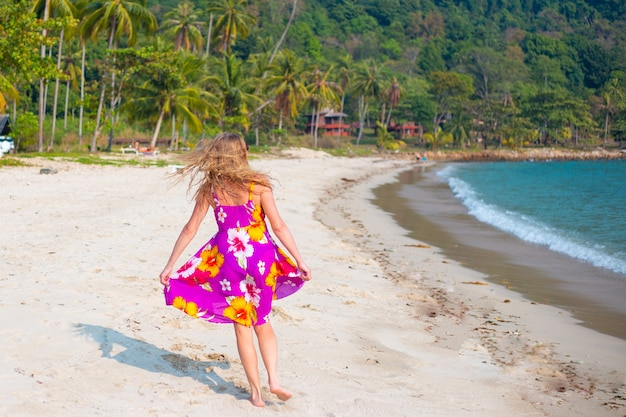 Женщина с длинными светлыми волосами в ярком платье бежит по песчаному берегу тропического острова