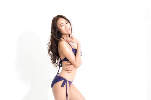Woman with long brown hair wearing purple bikini dress in a summer fashion isolated on white.