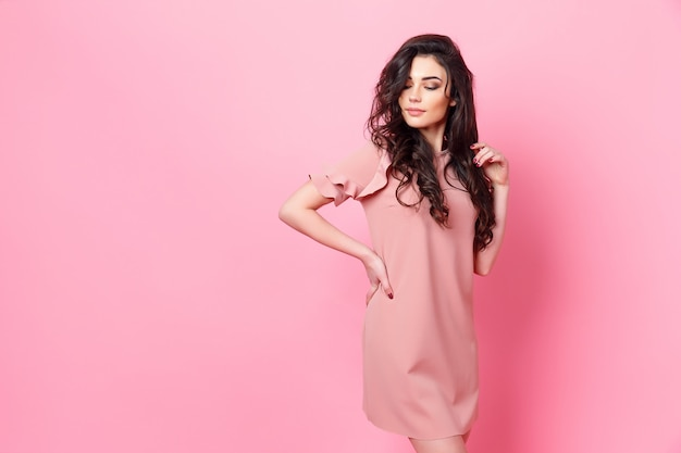 Woman with long curly hair in a pink dress.