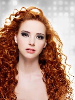 긴 곱슬 머리와 세련된 보라색 메이크업을 가진 여자. 깜박이는 배경. 보케
