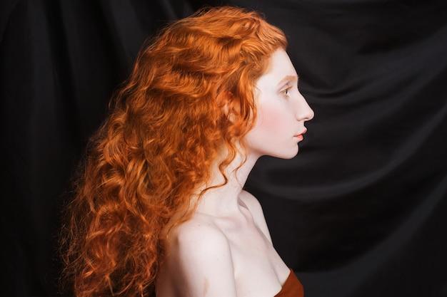 黒の背景に長い巻き毛の赤い流れる髪を持つ女性。淡い肌、青い目、化粧せずに明るく異常な外観の赤い髪の少女。自然の美。ルネッサンス時代の少女