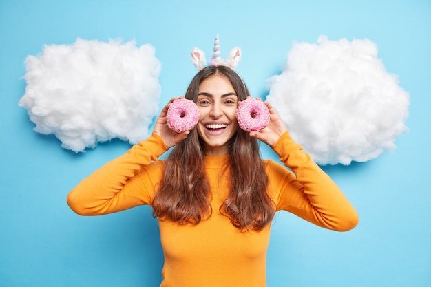 Woman with long dark hair holds two delicious doughnuts near face smiles positivelty has sweet tooth feels happy isolated on blue