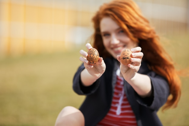 Woman with long ginger hair showing two painted easter eggs