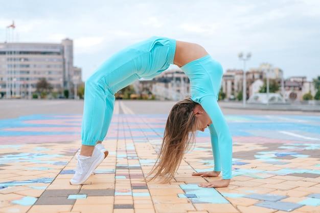 Женщина с длинными волосами и стройным телом делает утренние упражнения йоги на коврике для йоги на белой деревянной террасе поза йоги поза моста