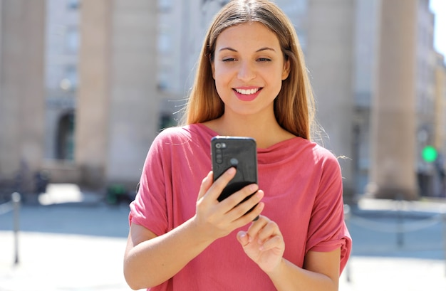 Woman with long hair chatting on smartphone in city street