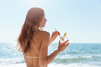 woman with long hair, holding a wine glass with cocktail, spending vacation