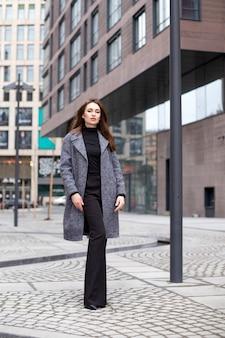 코트에 긴 머리를 가진 여자는 도시에서 산책. 여자는 회색 코트와 검은 바지를 입고 있습니다. 라이프 스타일, 스트리트 스타일