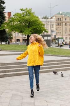 黄色いレインコートを着た長い髪の女性が走り、散歩で街中を笑顔