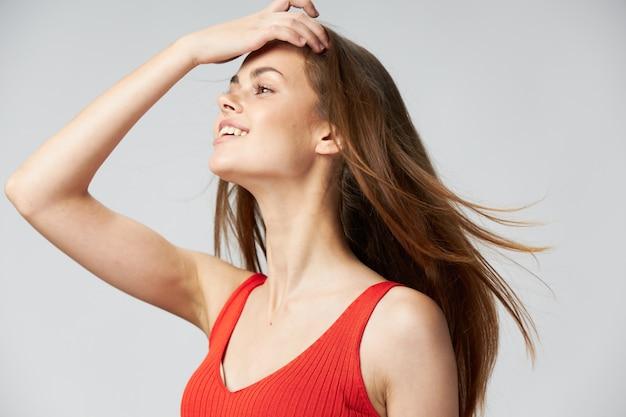 長い髪の女性は手と赤いタンクトップで彼女の頭に触れています