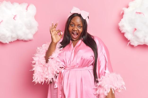 긴 머리를 가진 여자는 괜찮은 제스처가 분홍색에 고립 된 나비 머리띠 세련된 드레싱 가운을 착용한다고 외친다.