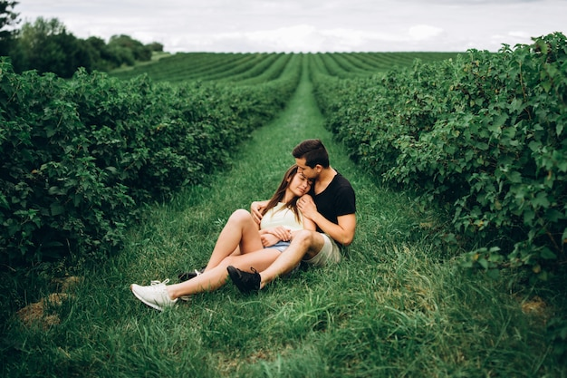 Woman with long hair and man sitting between currant bushes, hugging and kissing.