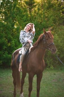 Женщина с длинными волосами позирует с коричневой лошадью в лесу на солнечном лугу