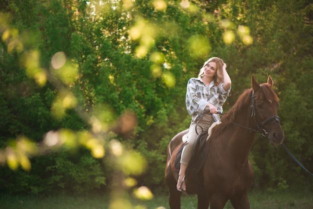 日当たりの良い牧草地の森で茶色の馬とポーズをとる長い髪の女性。
