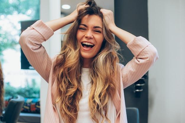 Женщина с длинными волосами, сидя в парикмахерской