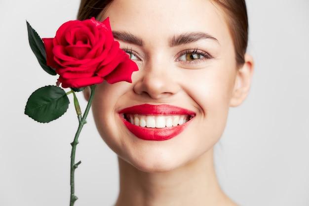 Женщина с длинными волосами улыбка роза крупным планом чистый фон кожи