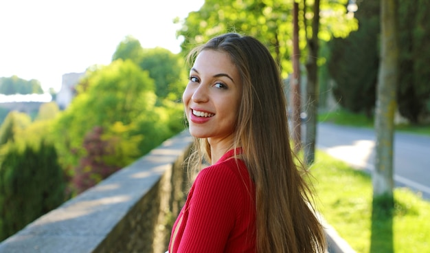 Woman with long hair turn the head and looking at camera