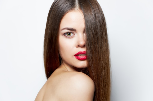 Woman with long hairstyle on the face lipstick close-up