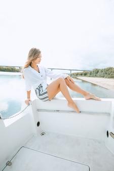 Женщина с длинными ногами в роскошной одежде, отдыхая на яхте в море