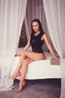 Woman with long legs sitting on bed