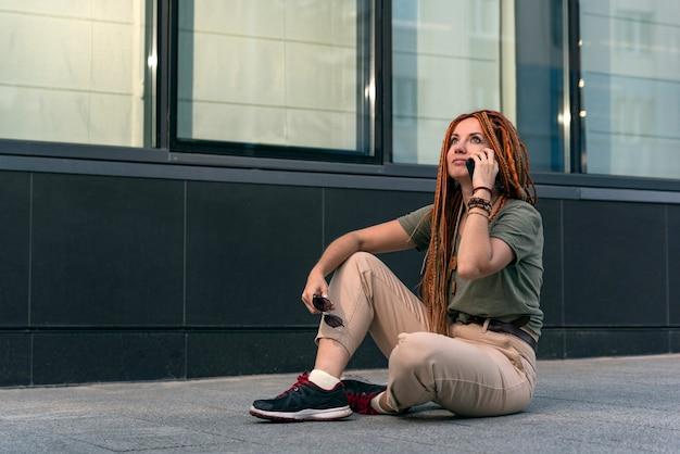 Женщина с длинными красными дредами задумчиво смотрит вверх во время разговора по телефону. офисное здание на фоне