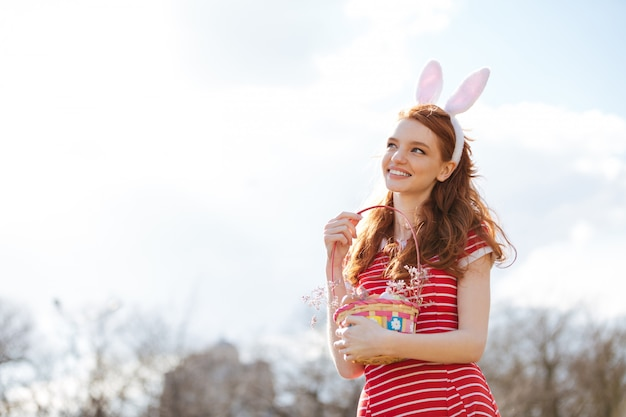 Woman with long red hair holding basket with painted eggs